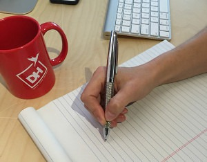 Picture of a hand writing on a note pad
